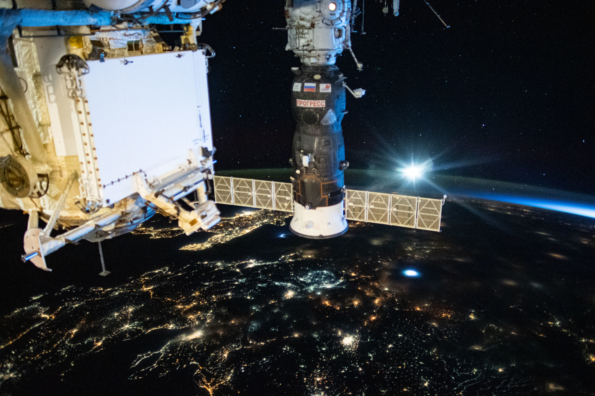 Russia's Progress 76 resupply ship is pictured docked to the International Space Station's Pirs docking compartment. Below the orbiting lab are the city lights of southeastern Europe.