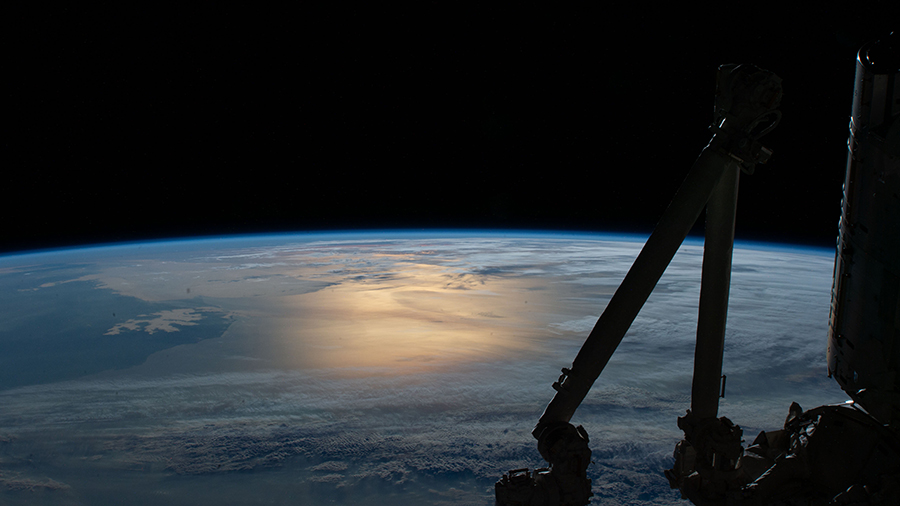 Flying over southern Argentina, this photograph from the space station looks northward with the Sun's glint beaming on the Atlantic Ocean.