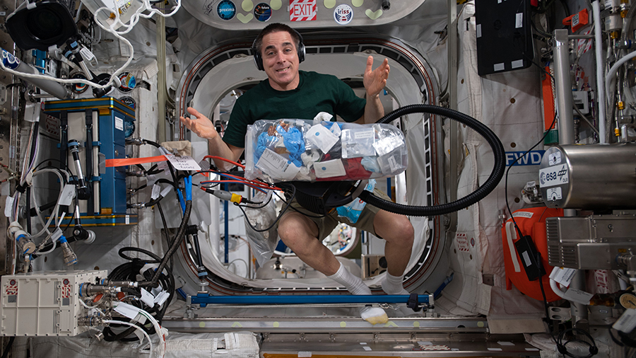 Expedition 63 Commander Chris Cassidy collects trash for disposal during weekend housekeeping activities aboard the space station.