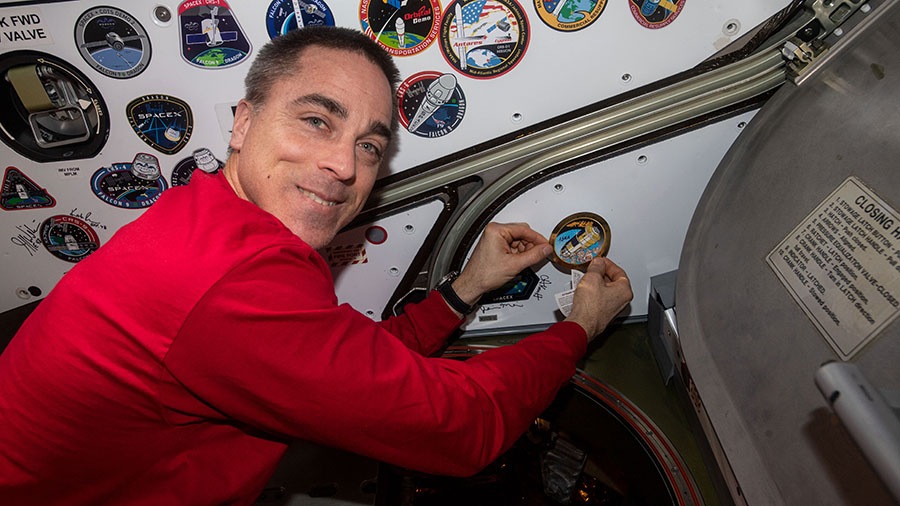 Expedition 63 Commander Chris Cassidy applies a mission sticker inside the space station to signify the departure of Japan's HTV-9 resupply ship from the U.S. Harmony module.