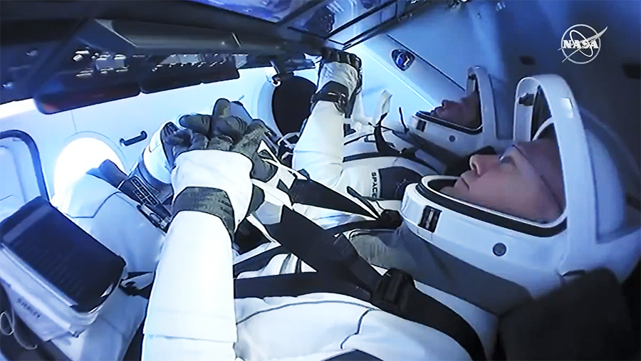 Astronauts (front to back) Doug Hurley and Bob Behnken are suited up inside the SpaceX Crew Dragon preparing for splashdown.