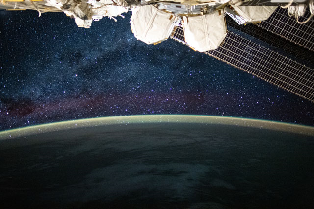 This long-exposure photograph from the International Space Station was taken during an orbital night period and reveals the Milky Way glittering above a bright but exaggerated atmospheric glow that blankets the Earth's horizon. Credits: NASA