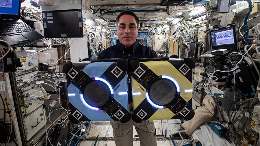 Expedition 63 Commander Chris Cassidy poses with two Astrobee robotic assistants during visual and navigation tests inside the Kibo laboratory module.