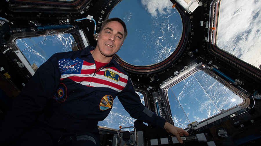 Expedition 63 Commander Chris Cassidy poses for a portrait wearing his flight suit inside the cupola, the International Space Station's window to the world.