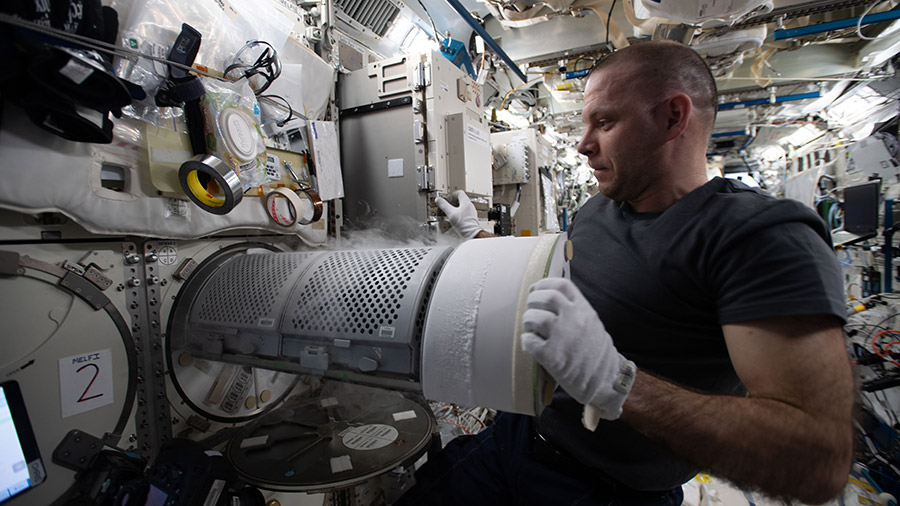 Expedition 63 Flight Engineer Ivan Vagner transfers biological samples into a science freezer for stowage and later analysis aboard the International Space Station.