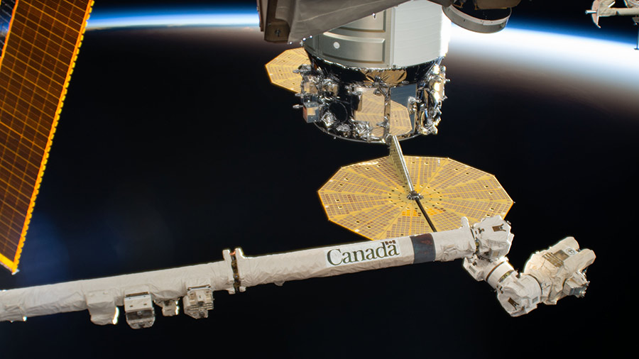 The Canadarm2 robotic arm is extended near the Northrop Grumman Cygnus resupply ship with its prominent cymbal-shaped UltraFlex solar arrays.