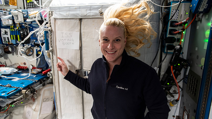 "NASA astronaut and Expedition 64 Flight Engineer Kate Rubins points to the International Space Station's ""voting booth"" where she cast her vote from space this month."