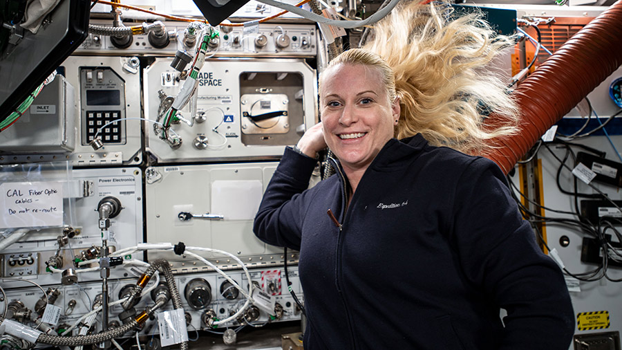 NASA astronaut and Expedition 64 Flight Engineer Kate Rubins poses for a photograph with a variety of space research gear and science racks behind her.