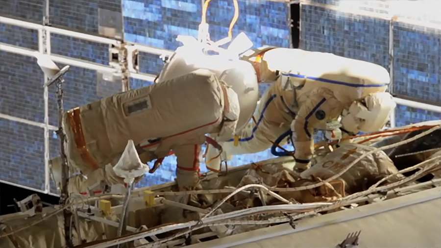 An external station camera captures spacewalkers (from left) Sergey Ryzhikov and Sergey Kud-Sverchkov readying the orbiting lab for a new Russian module.