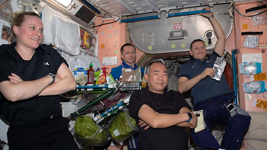Four Expedition 64 crew members are pictured relaxing after a meal at the end of the work day inside the Unity module.