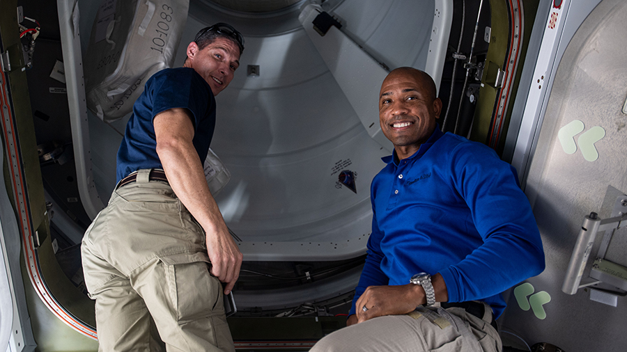 NASA astronauts (from left) Michael Hopkins and Victor Glover are pictured before opening the hatch to the newly docked SpaceX Cargo Dragon vehicle.