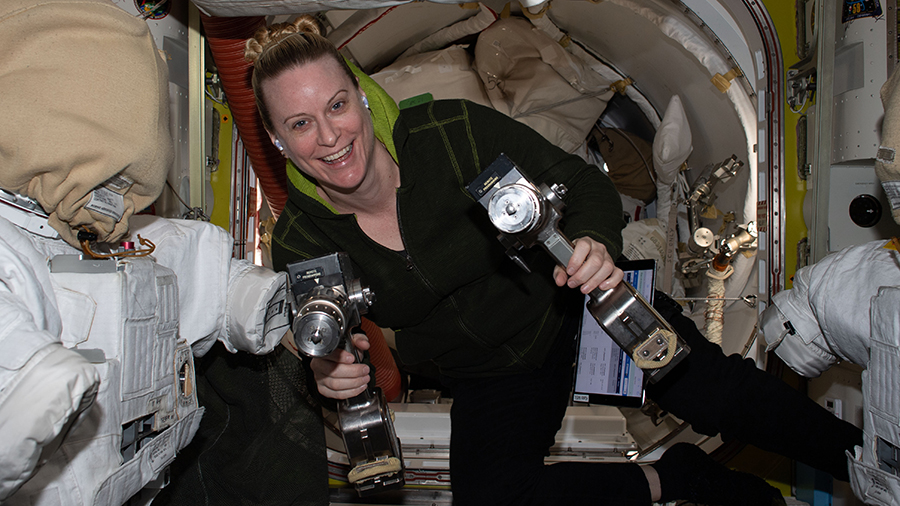 Expedition 64 Flight Engineer Kate Rubins is pictured inside the U.S. Quest airlock carrying a pair of pistol grip tools used for maintenance work during spacewalks.