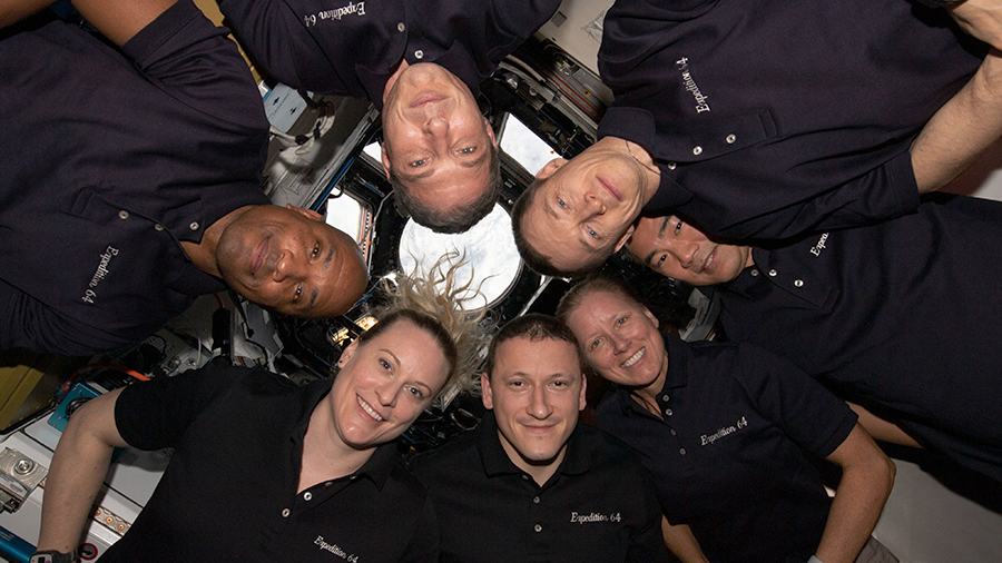 "The seven-member Expedition 64 crew gathers together for a New Year's Day portrait inside the International Space Station's ""window to the world,"" the cupola."