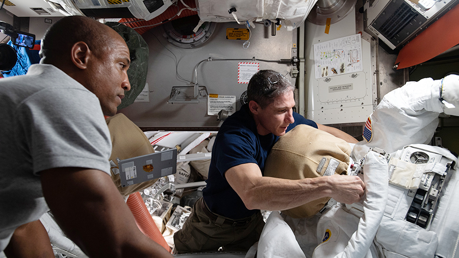 NASA astronauts Victor Glover (left) and Michael Hopkins work on U.S. spacesuit maintenance inside the International Space Station's Quest airlock.