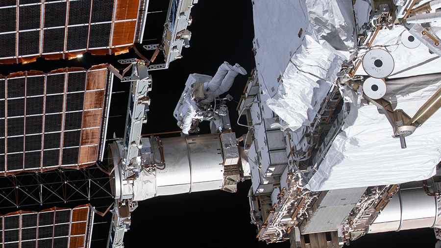 NASA spacewalker Flight Engineer Victor Glover is dwarfed by the main solar arrays on the International Space Station's far port-side truss structure.