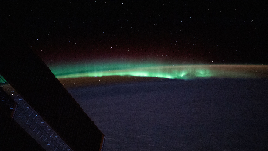 Earth's atmospheric glow and the aurora blanket the horizon as the space station orbited above the North Atlantic.