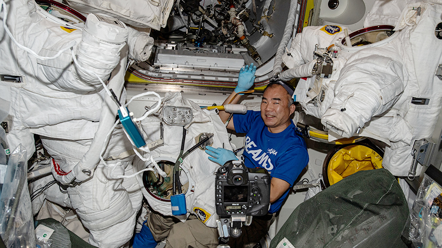 JAXA (Japan Aerospace Exploration Agency) astronaut Soichi Noguchi works on U.S. spacesuit gear inside the Quest airlock.