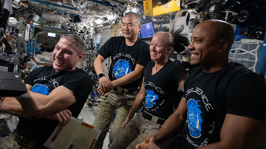 (From left) Michael Hopkins of NASA, Soichi Noguchi of JAXA (Japan Aerospace Exploration Agency), and NASA astronauts Shannon Walker and Victor Glover gather around a laptop computer to watch a movie inside the U.S. Destiny laboratory module.