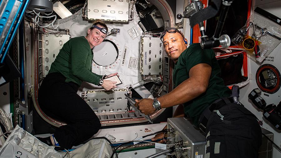 NASA astronauts Kate Rubins and Victor Glover work on the new NanoRacks Bishop airlock.