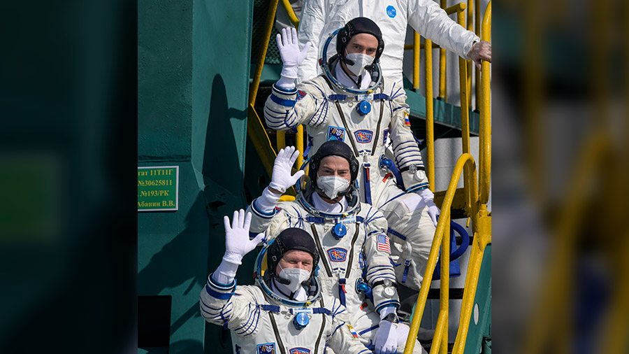 (From top to bottom) Expedition 65 crew members Pyotr Dubrov, Oleg Novitskiy and Mark Vande Hei wave bye before boarding their Soyuz MS-18 rocket for a liftoff to the space station.