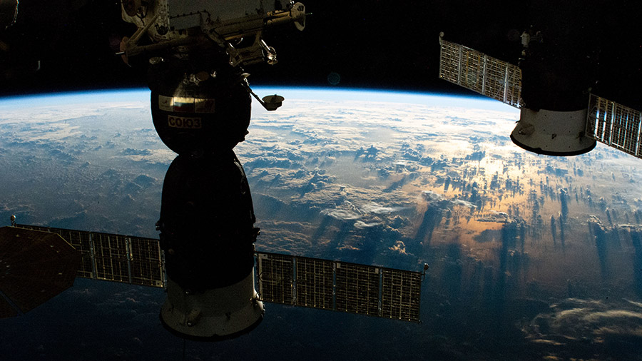 (From left) A Russian crew ship and a Russian cargo craft are pictured docked to the station as it orbited into a sunrise above the South Pacific.