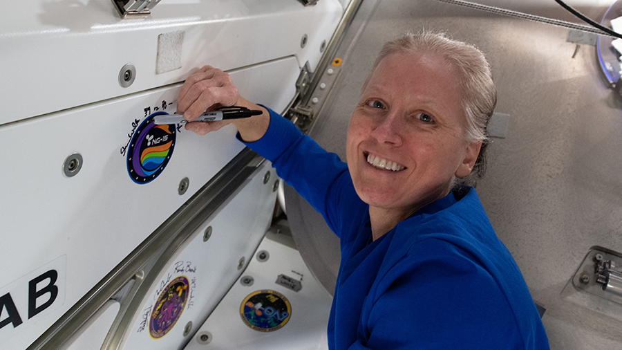 NASA astronaut Shannon Walker, seen here signing the Unity module's vestibule that leads to the Cygnus space freighter, will command the station till her departure at the end of April.