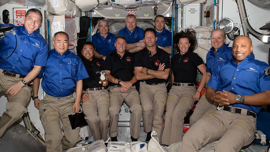 The 11-member crew aboard the station is actually a combination of three different crews: the Soyuz MS-18 crew in the back row, the SpaceX Crew-2 in the middle row, and the four SpaceX Crew-1 astronauts in the far left and right corners.