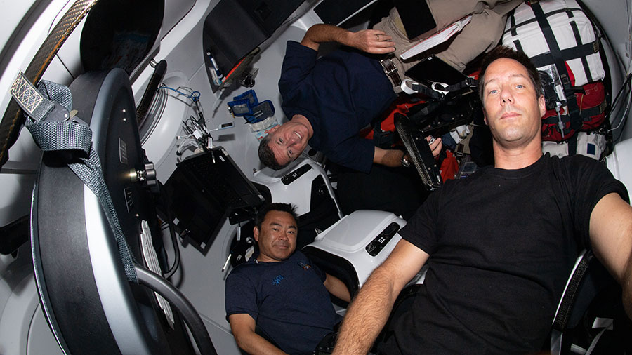 Expedition 65 astronauts (clockwise from bottom) Akihiko Hoshide, Shane Kimbrough and Thomas Pesquet are pictured inside the SpaceX Crew Dragon Resilience.