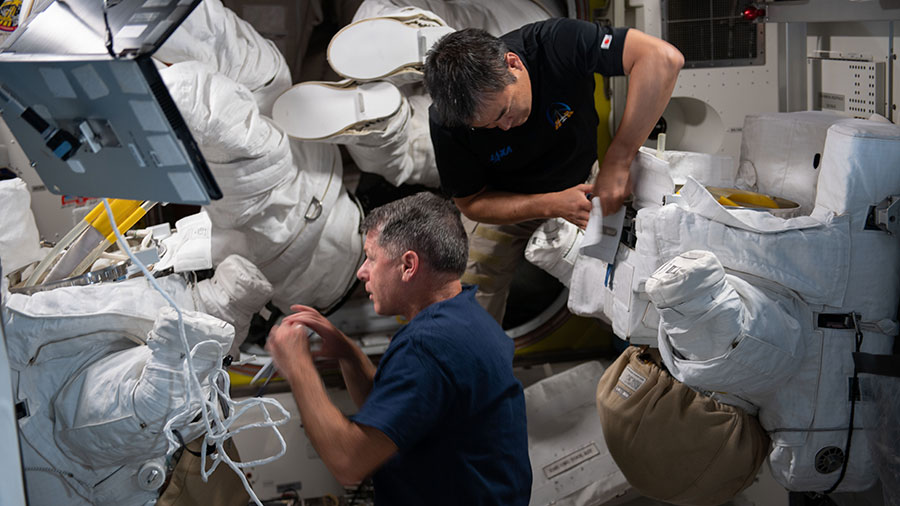Expedition 65 astronauts Shane Kimbrough and Akihiko Hoshide perform maintenance on a pair of U.S. spacesuits.