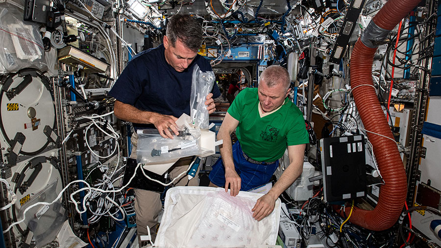 Expedition 65 Flight Engineers (from left) Shane Kimbrough and Oleg Novitskiy unpack science hardware for installation inside the U.S. Destiny laboratory module.