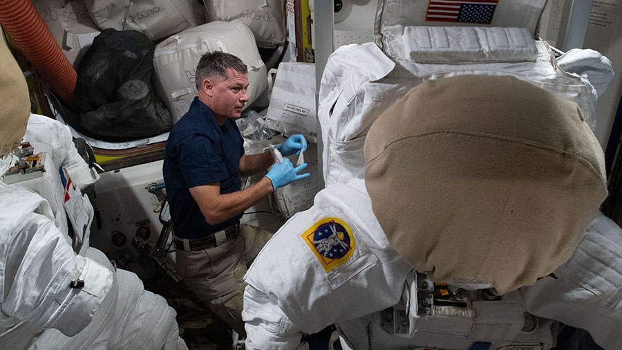 NASA astronaut Shane Kimbrough replaces life support components inside a U.S. spacesuit.
