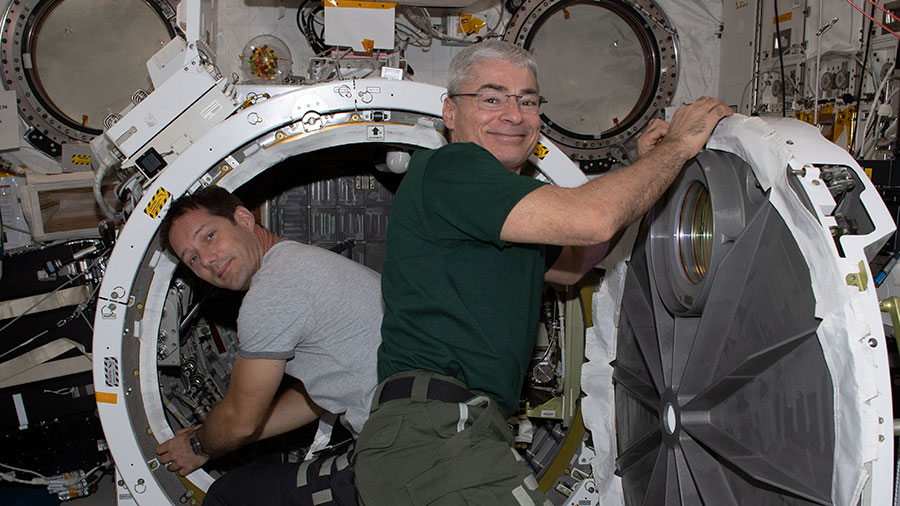 Astronauts (from left) Thomas Pesquet and Mark Vande Hei set up the Kibo laboratory module's airlock for the installation of an experiment platform.