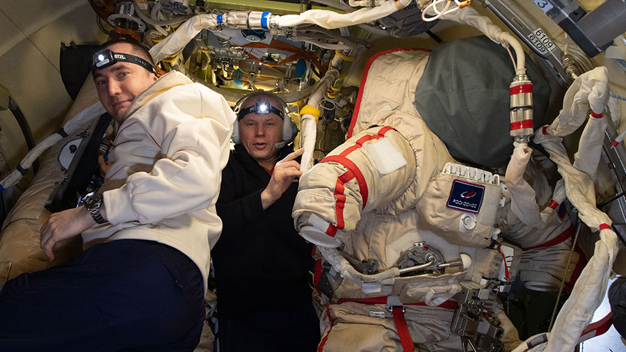 Cosmonauts (from left) Pyotr Dubrov and Oleg Novitskiy prepare Russian Orlan spacesuits inside the Poisk mini-research module for an upcoming spacewalk.