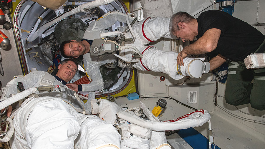 Expedition 65 Flight Engineer Mark Vande Hei assists astronauts Shane Kimbrough (bottom) and Thomas Pesquet (top) into their U.S. spacesuits to test them for a fit verification.