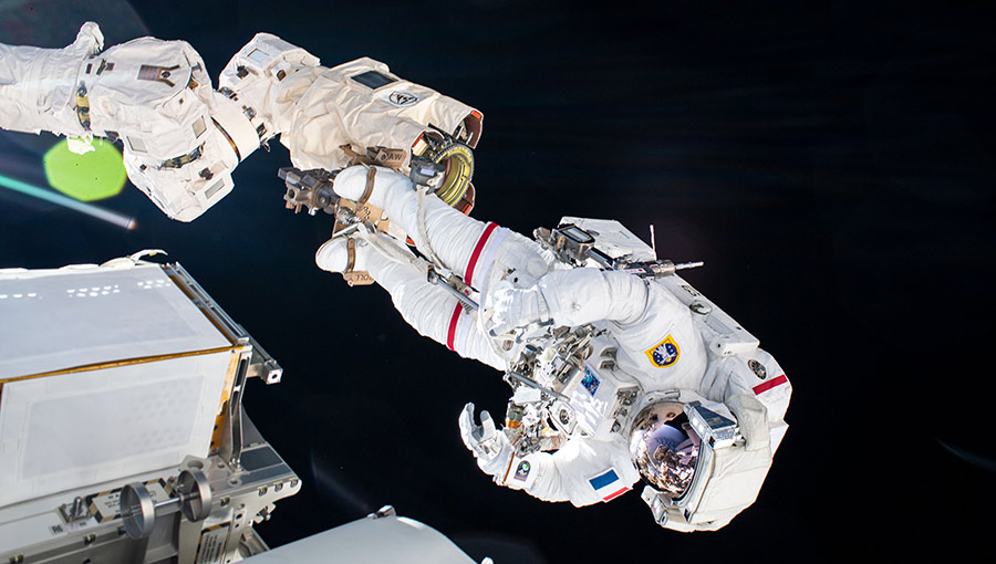 Astronaut Thomas Pesquet is pictured attached to the end of the Canadarm2 robotic arm during a spacewalk to install new roll out solar arrays.