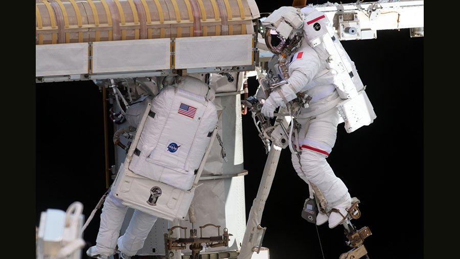 Spacewalkers (from left) Shane Kimbrough and Thomas Pesquet work to complete the installation of a roll out solar array on June 20, 2021,