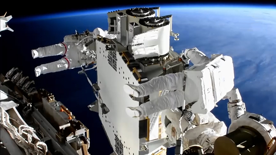 Spacewalkers Shane Kimbrough (foreground) and Thomas Pesquet work to prepare the second roll out solar array ready for installation an upcoming spacewalk.