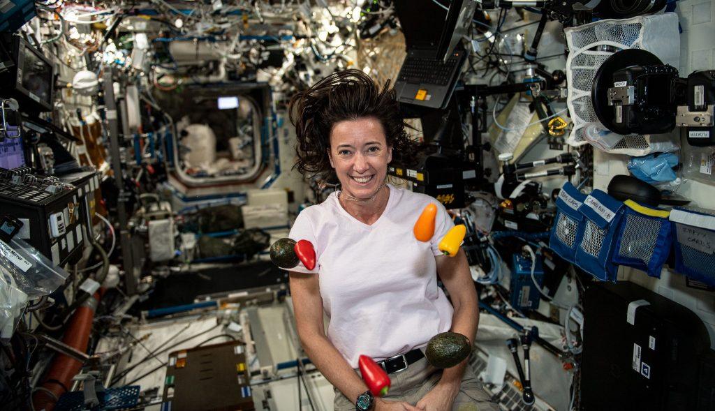Fresh vegetables float around NASA astronaut and Expedition 65 Flight Engineer Megan McArthur.