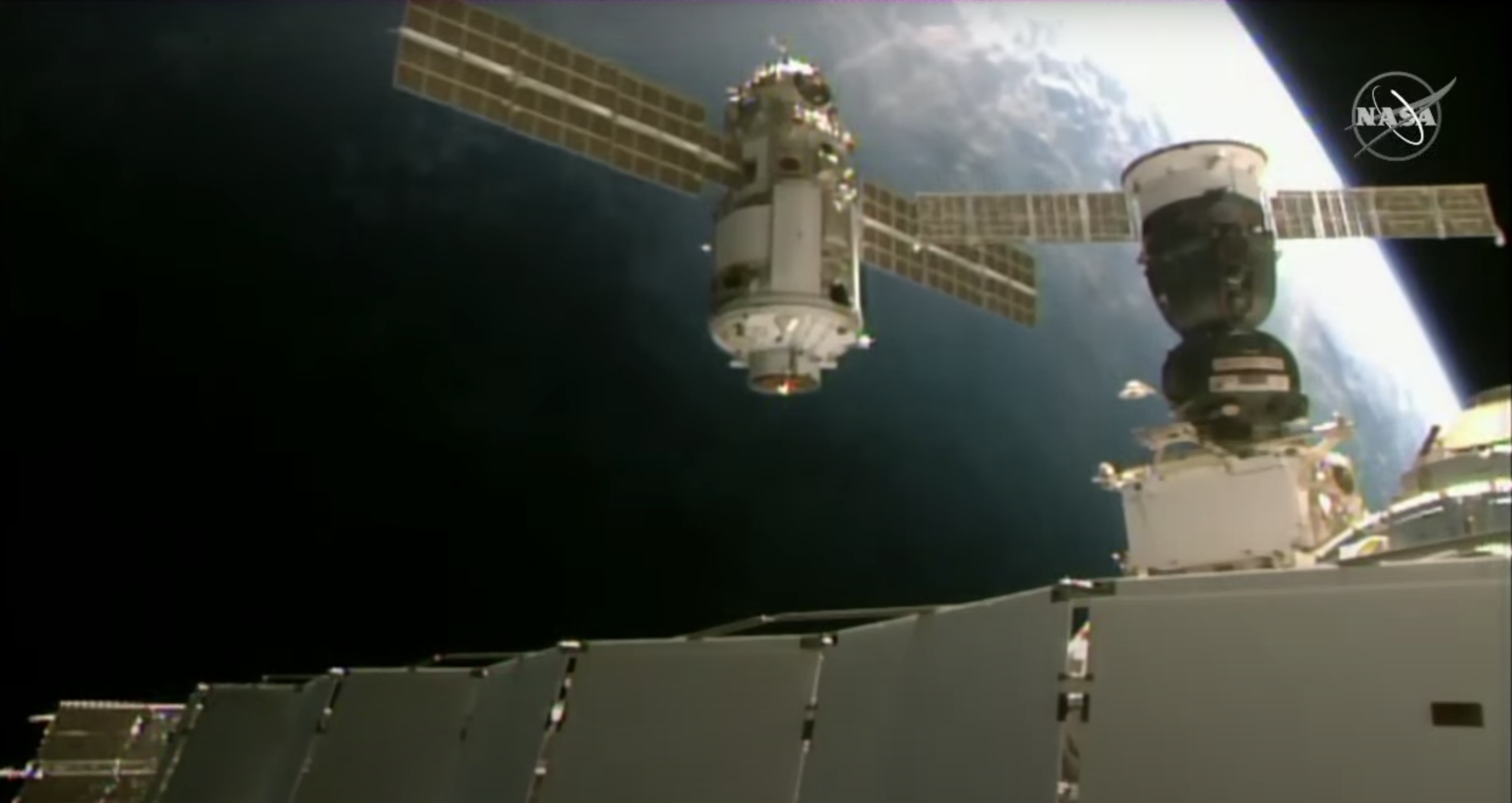 new module with solar panels flies near space station with Earth in background