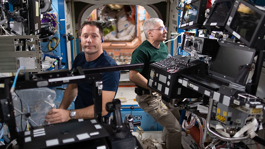 Astronauts (from left) Thomas Pesquet and Mark Vande Hei service a variety of hardware inside the U.S. Destiny laboratory module.