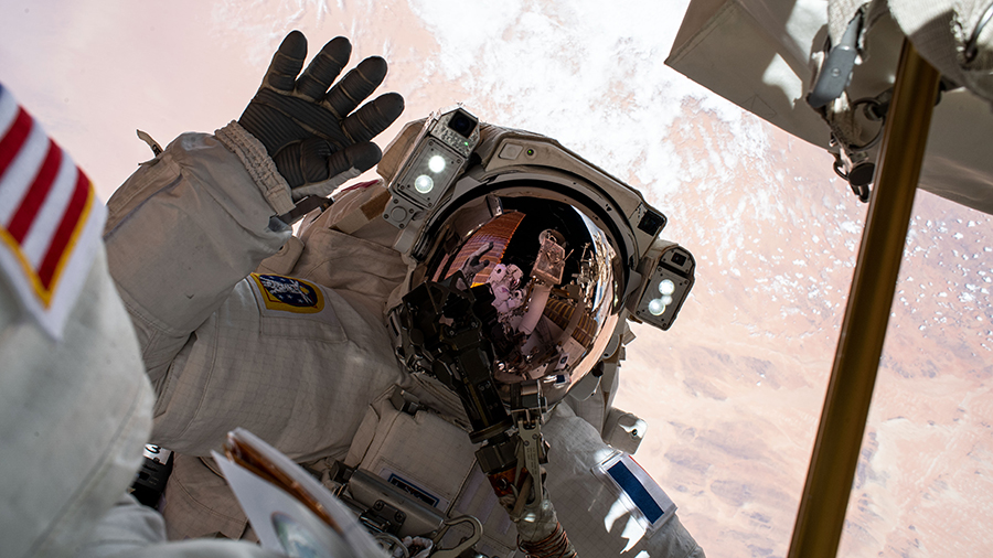 Astronaut Thomas Pesquet waves to the camera during a spacewalk to install Roll-Out Solar Arrays on June 25, 2021.