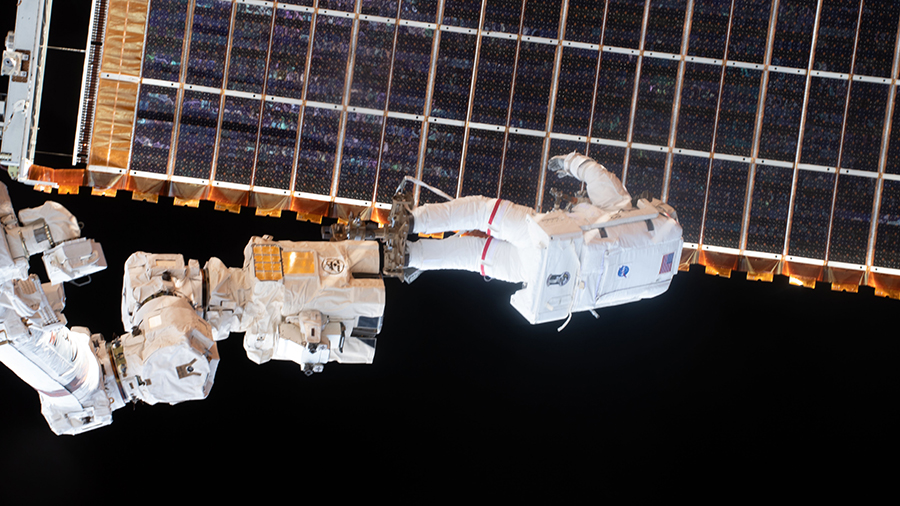 Spacewalker Thomas Pesquet is attached to the tip of the Canadarm2 robotic arm to install the station's second new solar array on June 25, 2021.