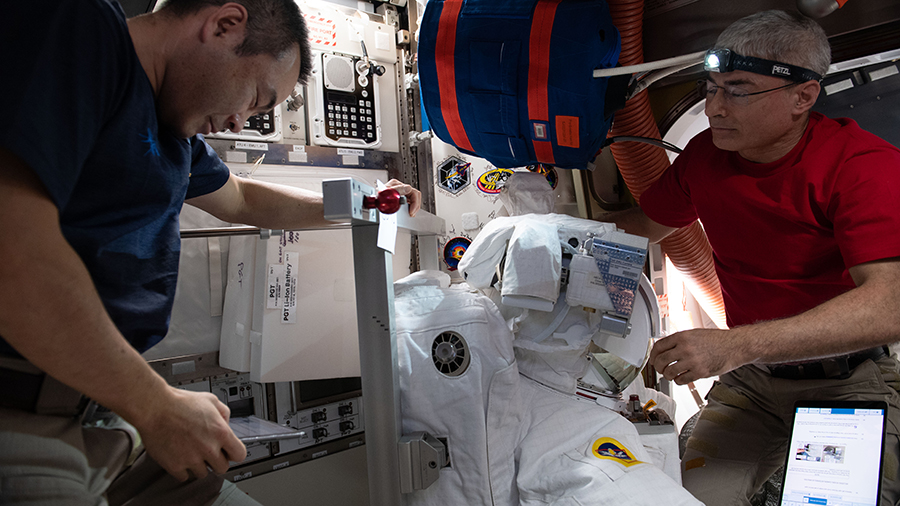 (From left) Astronauts Akihiko Hoshide and Mark Vande Hei install components on a U.S. spacesuit inside the U.S. Quest airlock.