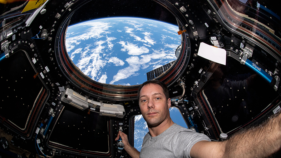 """Astronaut Thomas Pesquet is pictured inside the cupola, the space station's """"window to the world,"""" while orbiting above the Atlantic Ocean."""