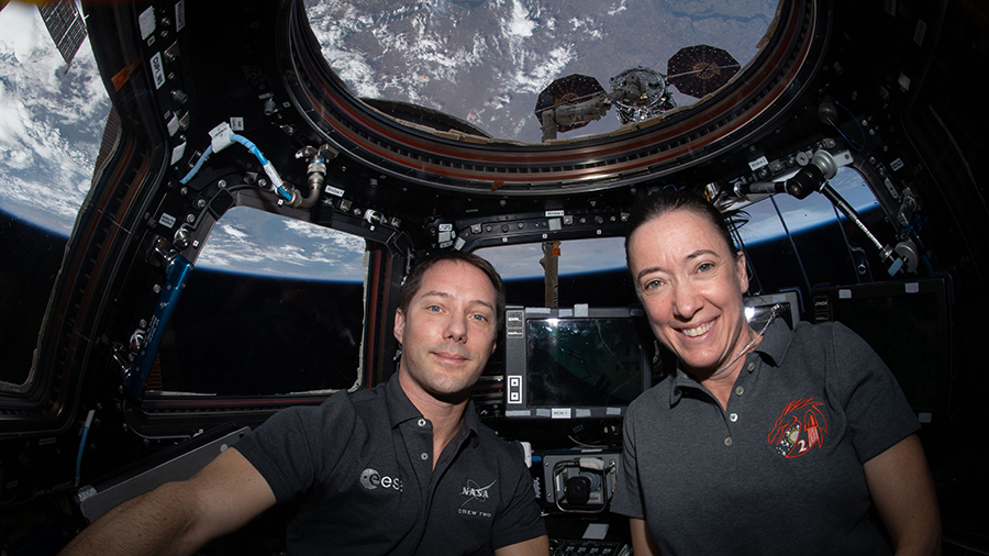 Astronauts Thomas Pesquet and Megan McArthur are inside the cupola with the Northrop Grumman Cygnus space freighter just outside behind them.