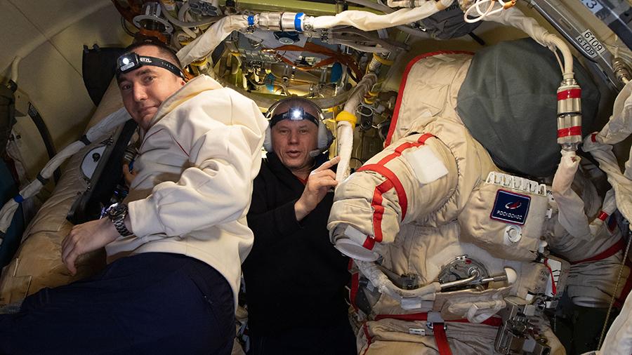 Cosmonauts (from left) Pyotr Dubrov and Oleg Novitskiy prepare Russian Orlan spacesuits.
