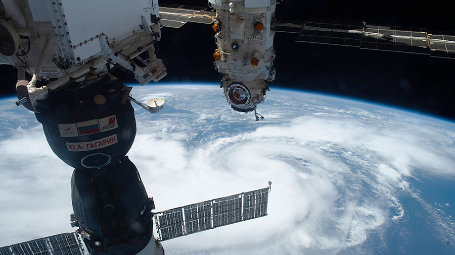 The Soyuz MS-18 crew ship and the Nauka multipurpose laboratory module are pictured above Hurricane Henri in the Atlantic Ocean on Aug. 21, 2021.