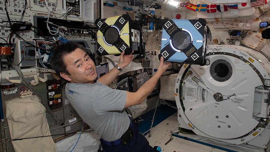 Astronaut Akihiko Hoshide checks out a pair of Astrobee robotic free-flyers inside the Kibo laboratory module.