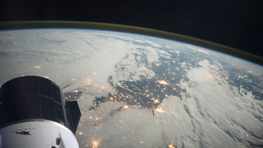 A portion of the SpaceX Cargo Dragon vehicle is pictured at lower left as the space station orbited above northern France.