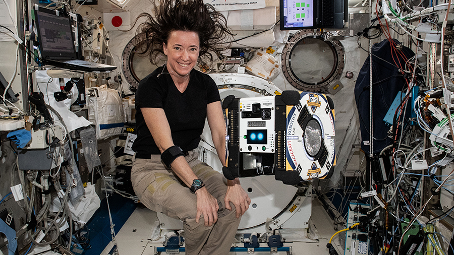 NASA astronaut Megan McArthur poses with an AstroBee robotic free-flying assistant inside the space station's Kibo laboratory module.